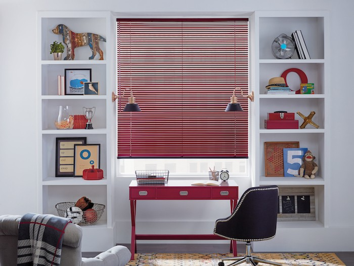 A home office with a red desk and red window blinds.